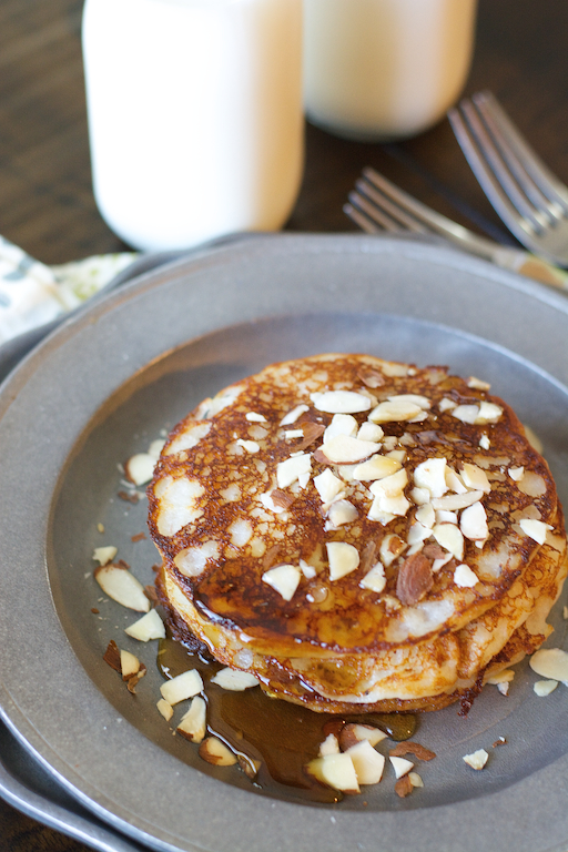 A stack of banana buttermilk pancakes on a metal plate.