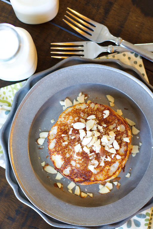 Overhead view of a stack of simple banana pancakes on a metal plate.