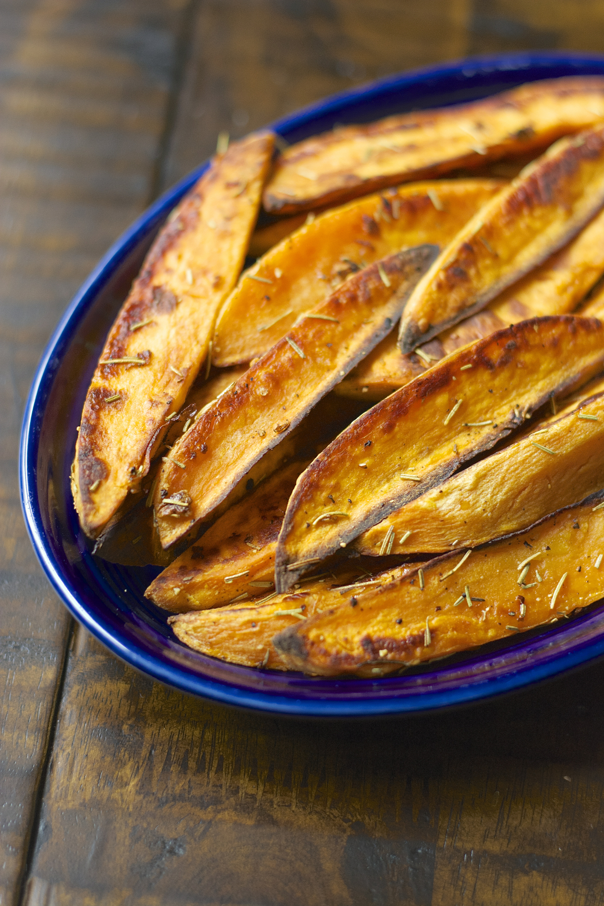 baked sweet potato wedges in a blue dish