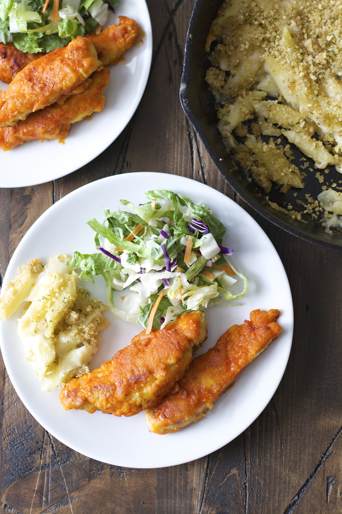 Overhead view of two plates of baked buffalo chicken tenders, salad, and mac n cheese.