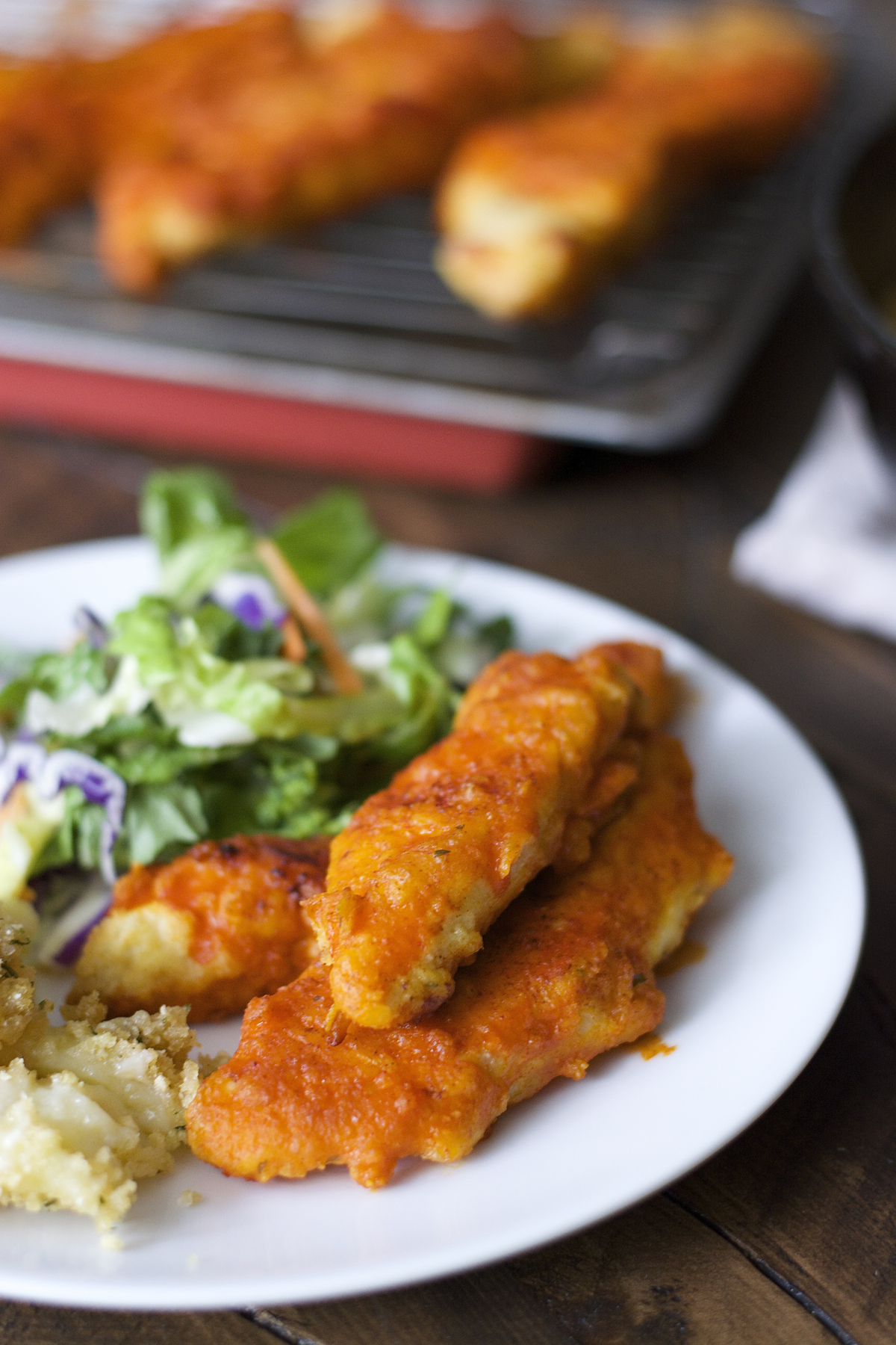 buffalo chicken tenders on a plate with side salad and mashed potatoes. More tenders rest in the background.