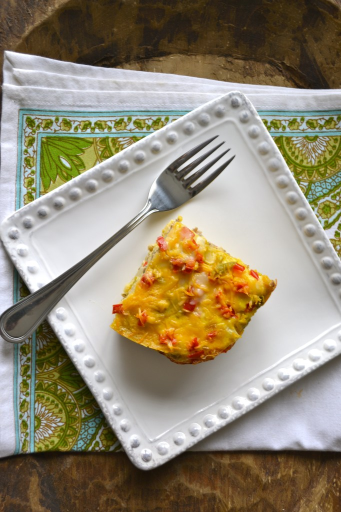 Overhead view of a slice of breakfast sausage casserole on a white plate with a fork.
