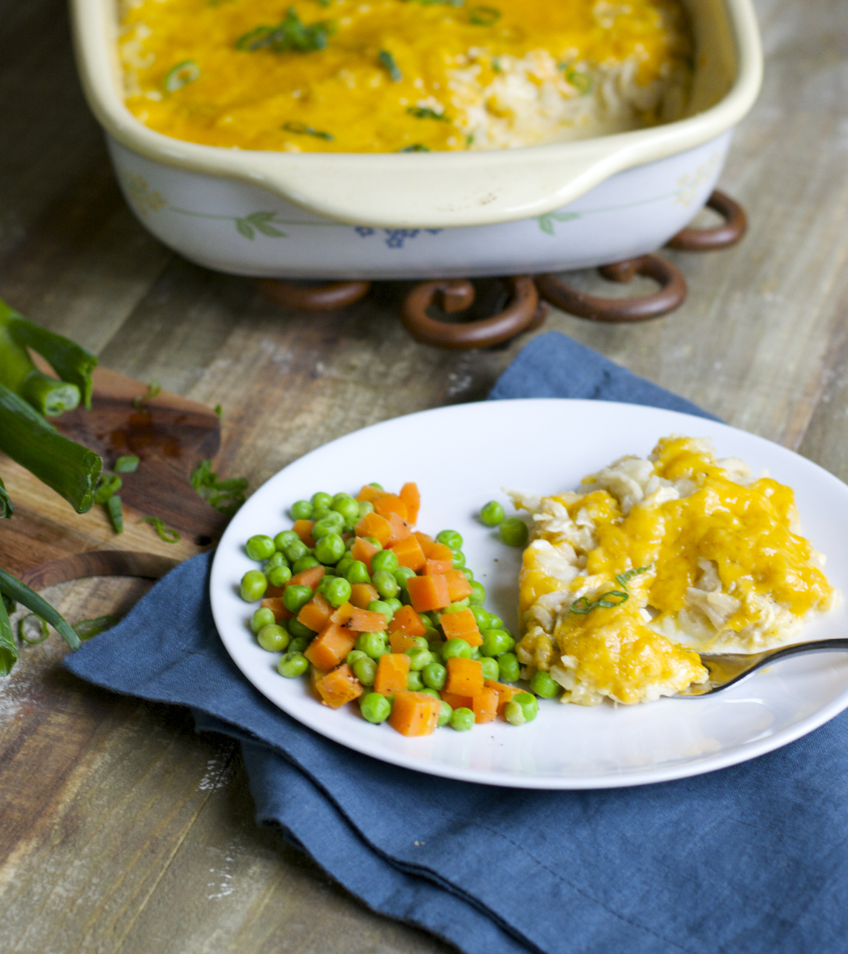 serving of cheesy chicken and rice casserole on a white plate with mixed peas and carrots. A baking dish of casserole rests in the background.