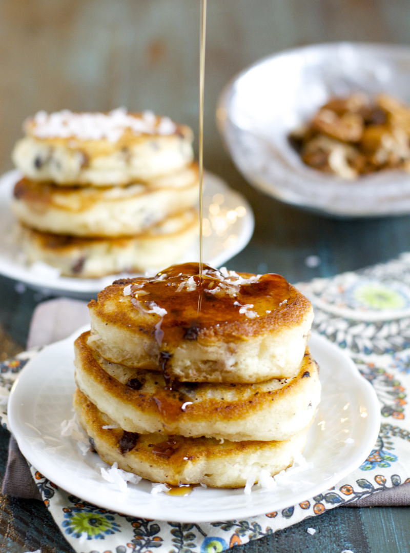 maple syrup being poured onto a stack of buttermilk chocolate chip pancakes.