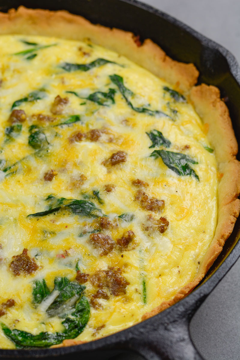 Close up of a keto spinach sausage quiche in a cast iron skillet