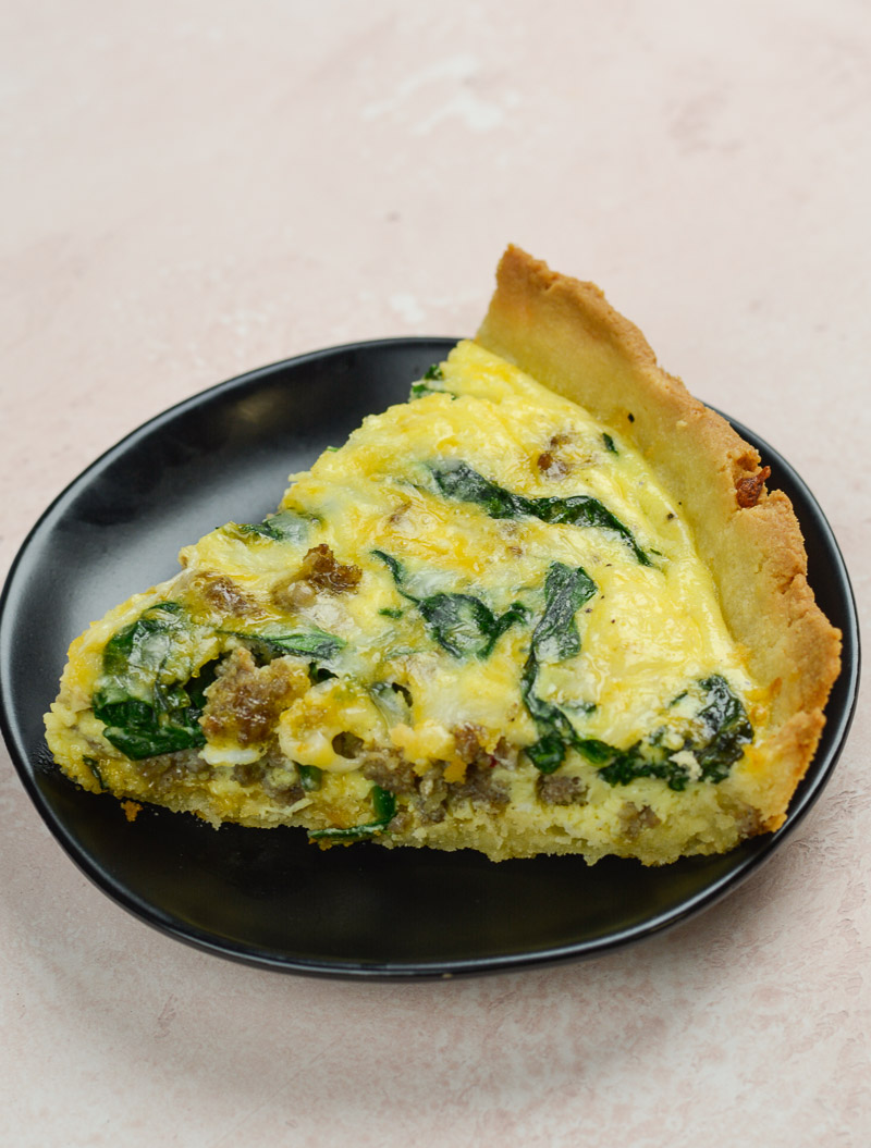 A slice of sausage spinach quiche on a dark plate