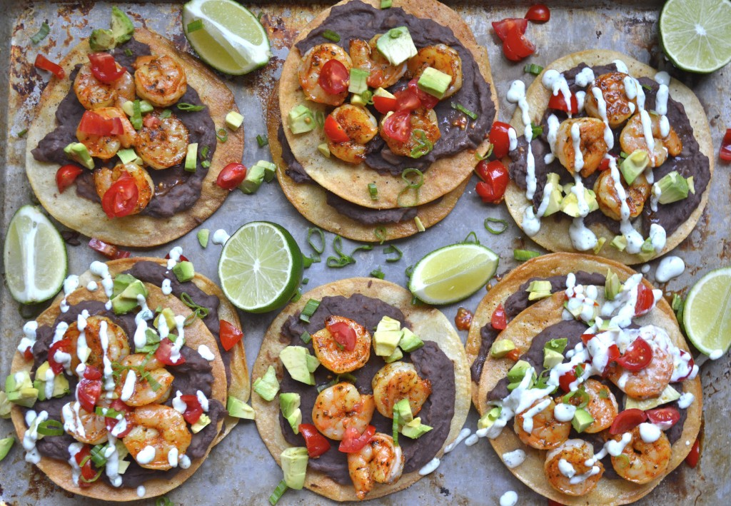 Overhead view of six homemade shrimp tostadas loaded with toppings.