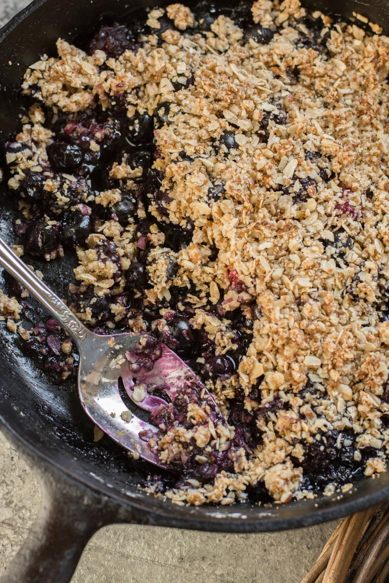a gluten free berry crisp in a cast iron skillet. A portion has been spooned out.