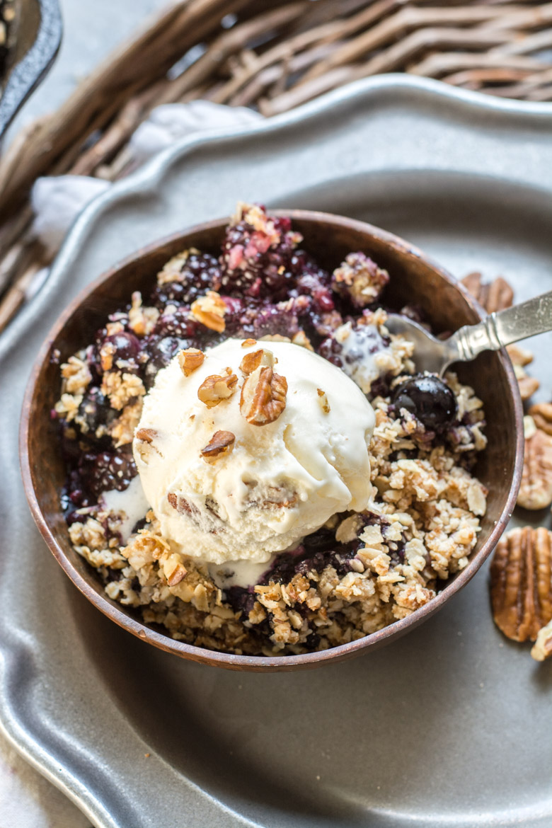a portion of mixed berry crisp topped with ice cream in a bowl