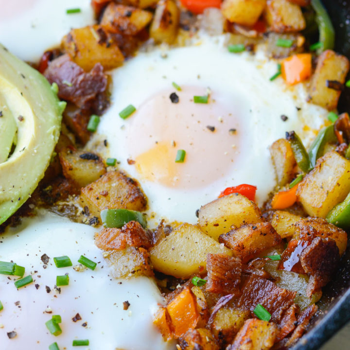 This Mexican Breakfast Hash is loaded with seasoned, crisp potatoes, peppers, onions, bacon and eggs! This is the perfect one pan breakfast recipe!
