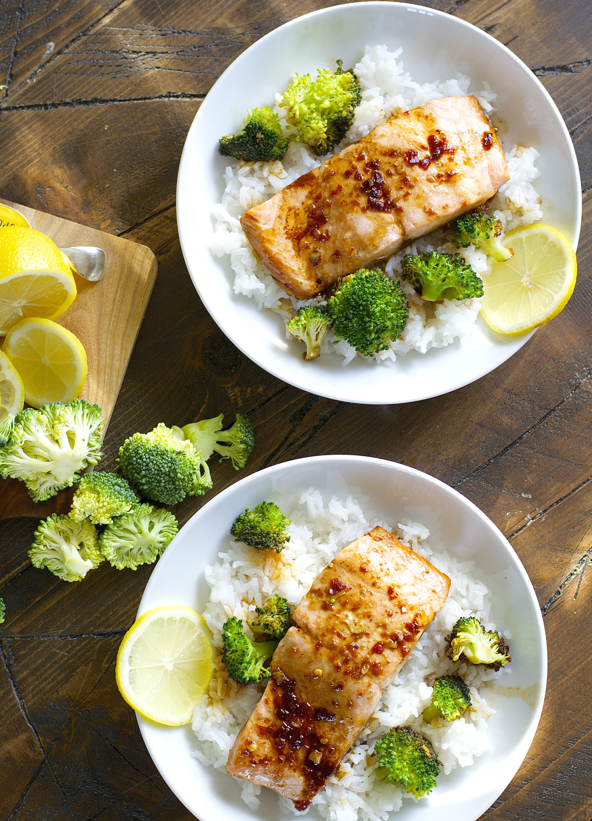 top view of two salmon rice bowls with broccoli and lemon slices