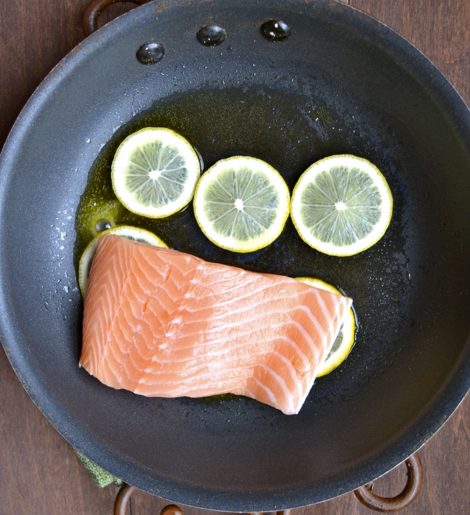 Top view showing raw salmon and lemon slices in a skillet
