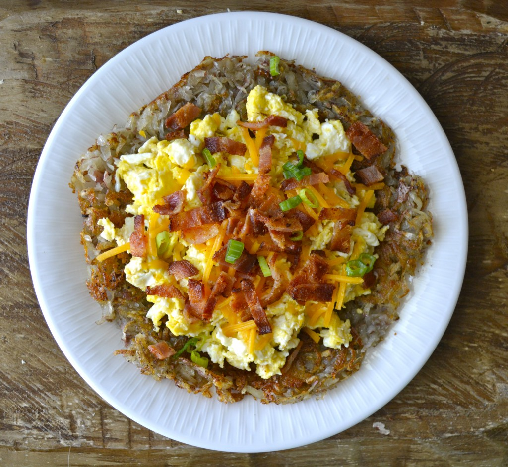 homemade hash browns on a plate topped with bacon and eggs