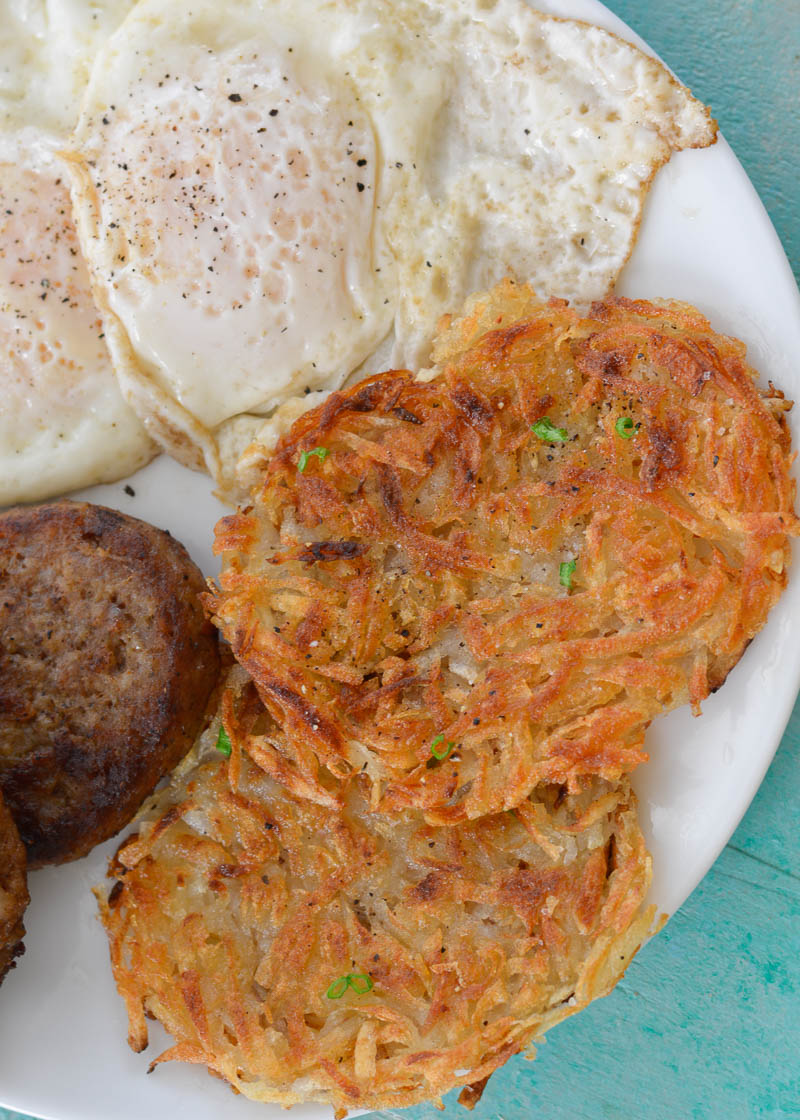 Two homemade hash browns on a white plate with a sausage and two fried eggs.