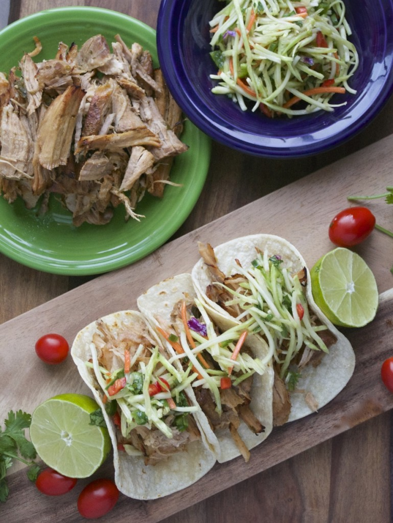 Overhead view of three slow cooker pork carnitas on a wooden board, next to jalapeno slaw.