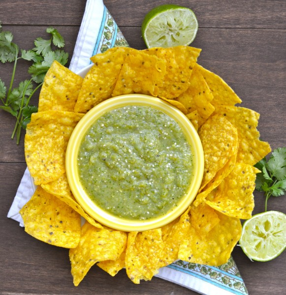 Overhead view of a dish of roasted tomatillo salsa surrounded by tortilla chips.