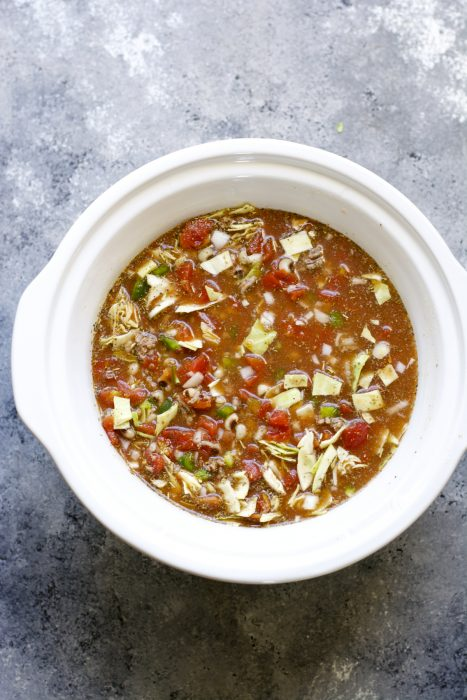 overhead view of black eyed peas and cabbage soup in a slow cooker insert