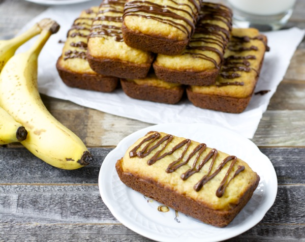 A mini loaf of gluten-free banana bread made with Bisquick. A pyramid of mini loaves and more bananas rest in the background.