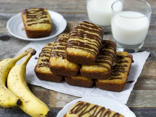 A pyramid of mini bisquick banana bread loaves drizzled with chocolate. Two glasses of milk rest in the background.