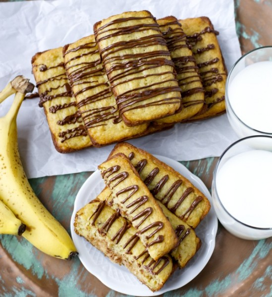 Overhead view of A pyramid of mini bisquick banana bread loaves drizzled with chocolate, two glasses or milk, and some bananas.