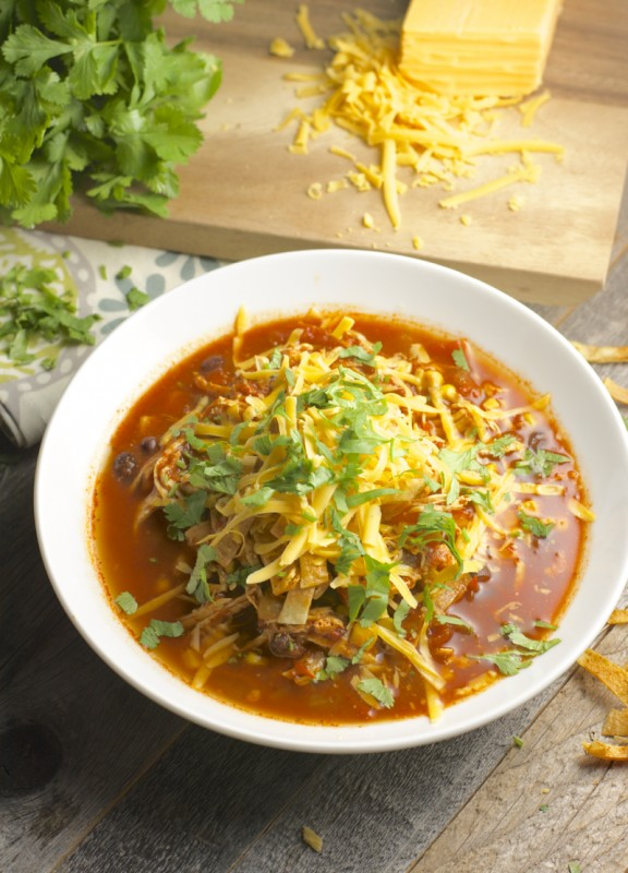 bowl of chicken enchilada soup garnished with cilantro and shredded cheese