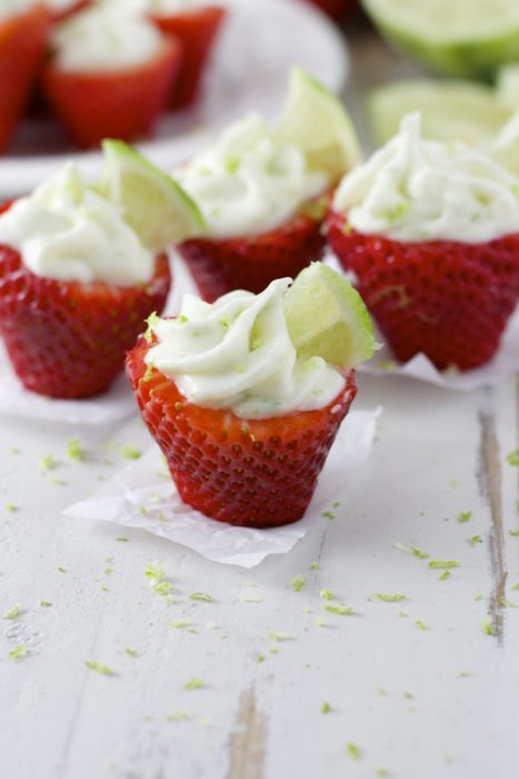 Four key lime stuffed strawberries, seen from the side.