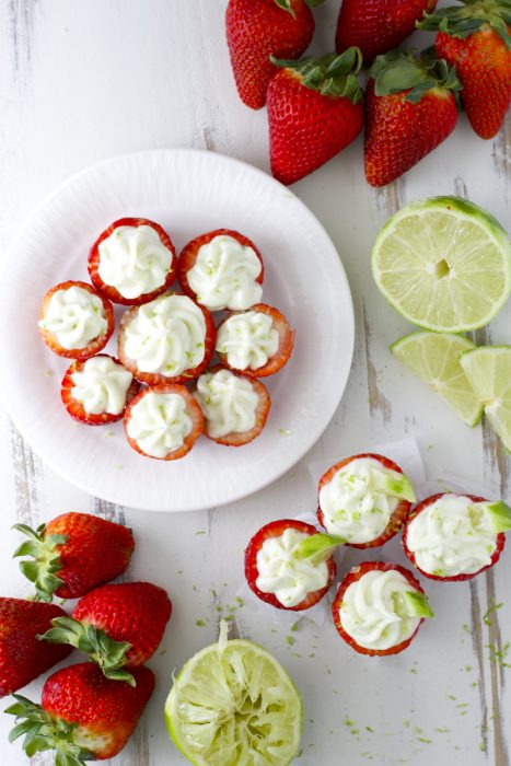 Overhead view of key lime cream cheese stuffed strawberries on a white plate. Four more are on the counter.