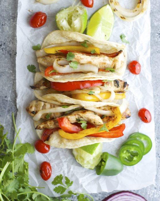 Overhead view of three grilled chicken fajitas on parchment paper.