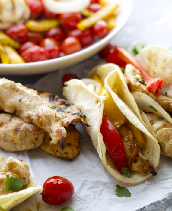Grilled chicken fajitas next to ingredients