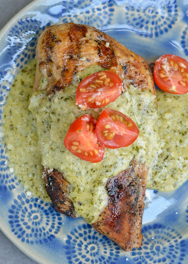 This Chicken with Pesto Cream Sauce is low carb comfort food at it's finest! Grilled Garlic Chicken is smothered with a Creamy Pesto Alfredo sauce making it a decadent keto-friendly dinner!
