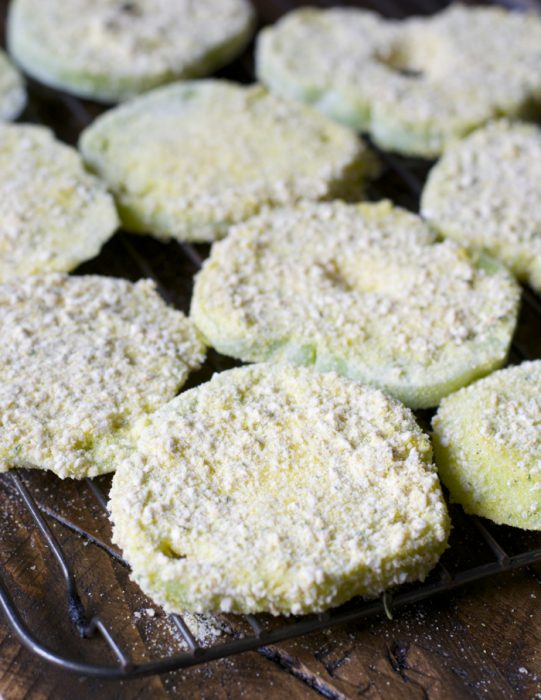 breaded green tomatoes on a cooling rack ready to be fried