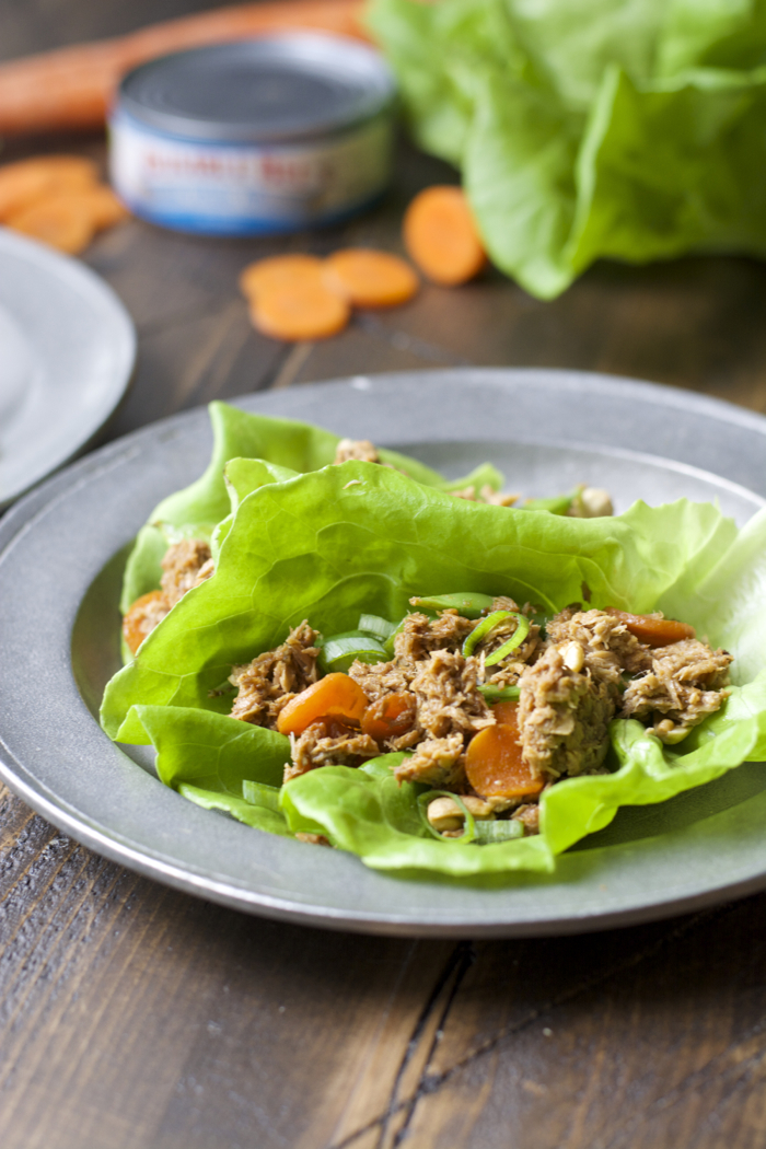 two tuna lettuce wraps on a gray plate. Cans of tuna and carrots rest in the background.