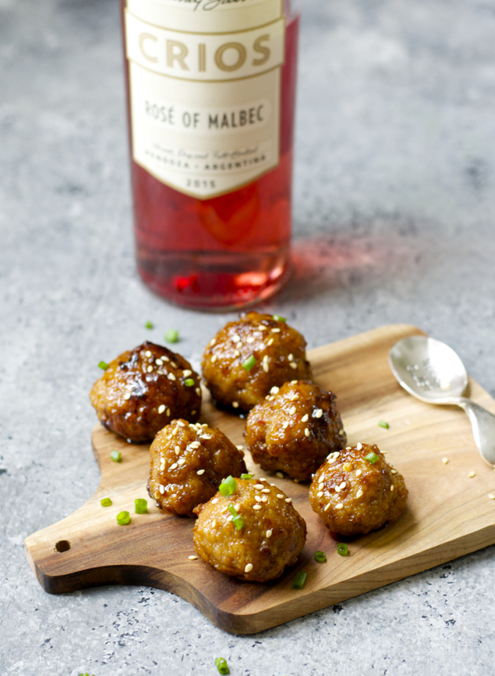 a cheese board with six Asian meatballs. a bottle of rose wine is in the background.