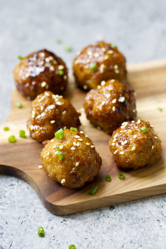 six asian style meatballs with spicy asian sauce on a wood cheese board