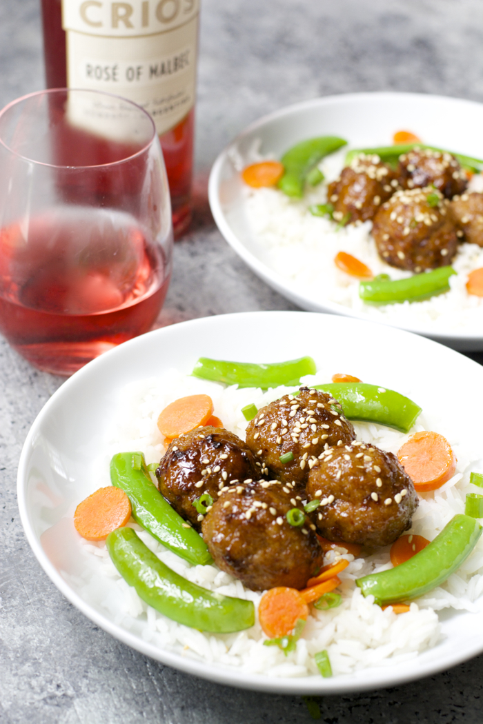 two plates of rice, veggies, and spicy asian meatballs next to a bottle of rose wine