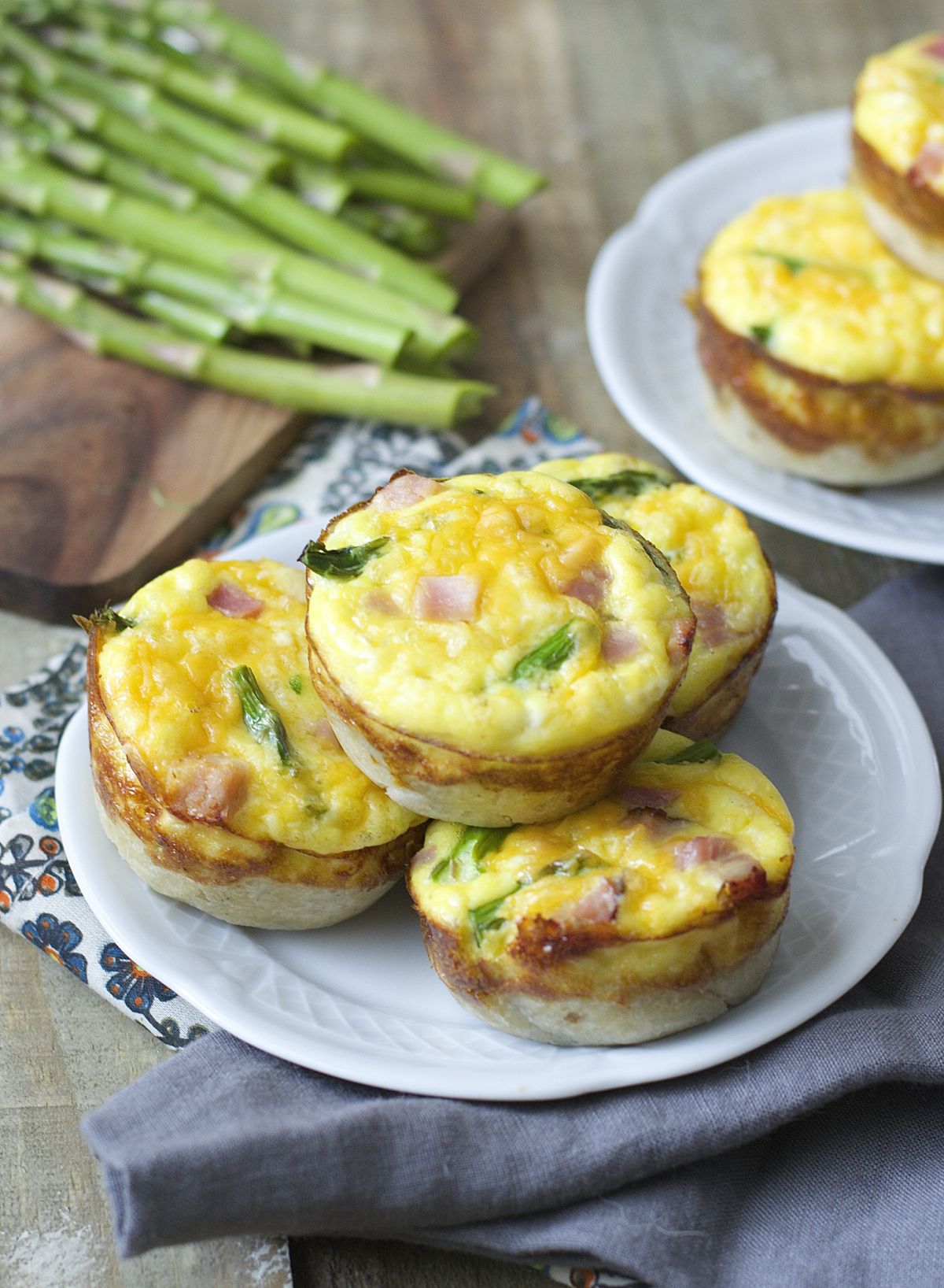 A stack of four ham and asparagus quiche on a white plate. Fresh asparagus spears rest in the background, along with another plate of mini quiche.