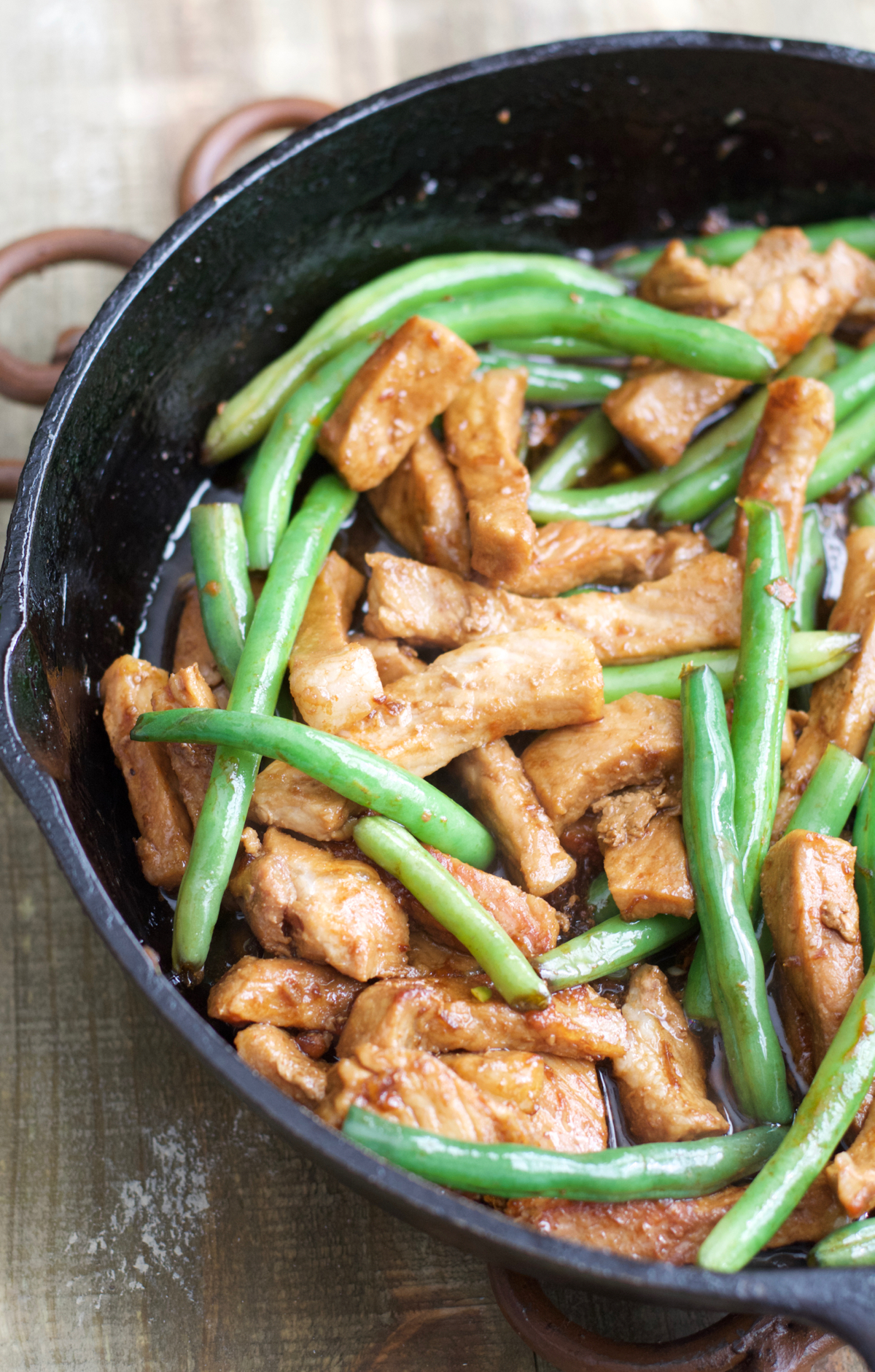 Green beans and sesame pork stir fry in a cast iron skillet.