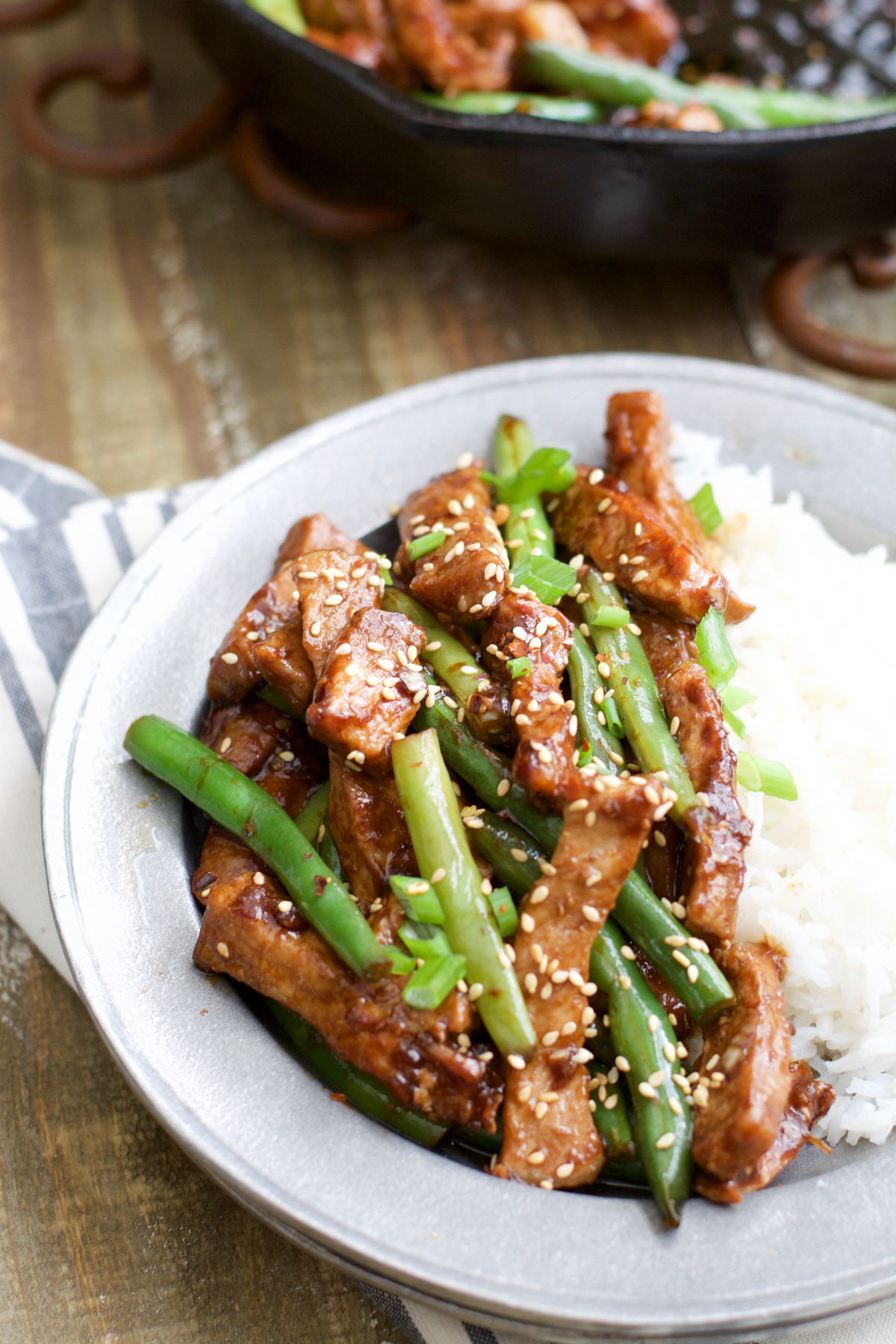 A plate of rice and sesame pork stir fry.
