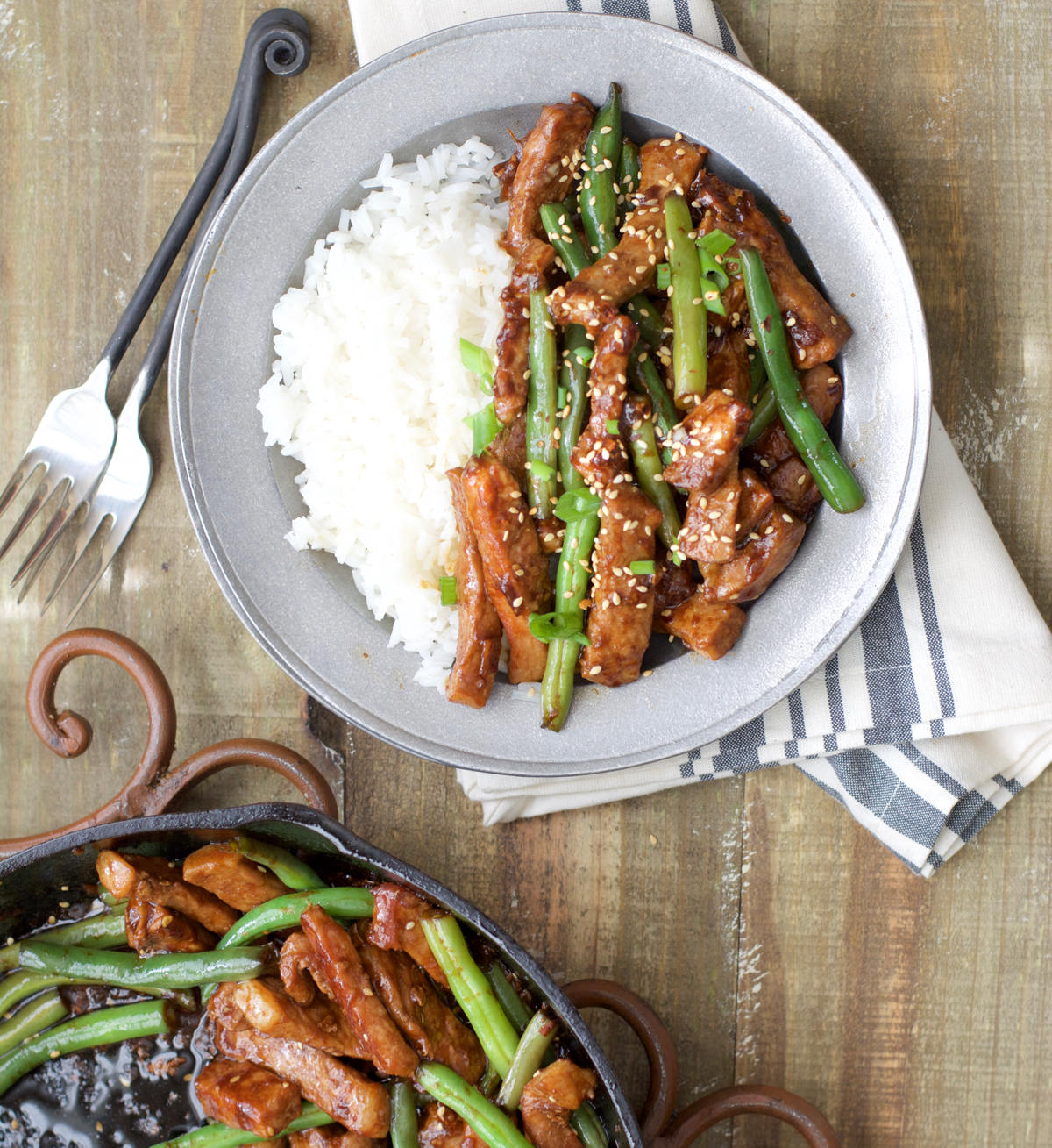 Overhead view of a portion of sesame pork chop stir fry with rice on a plate.