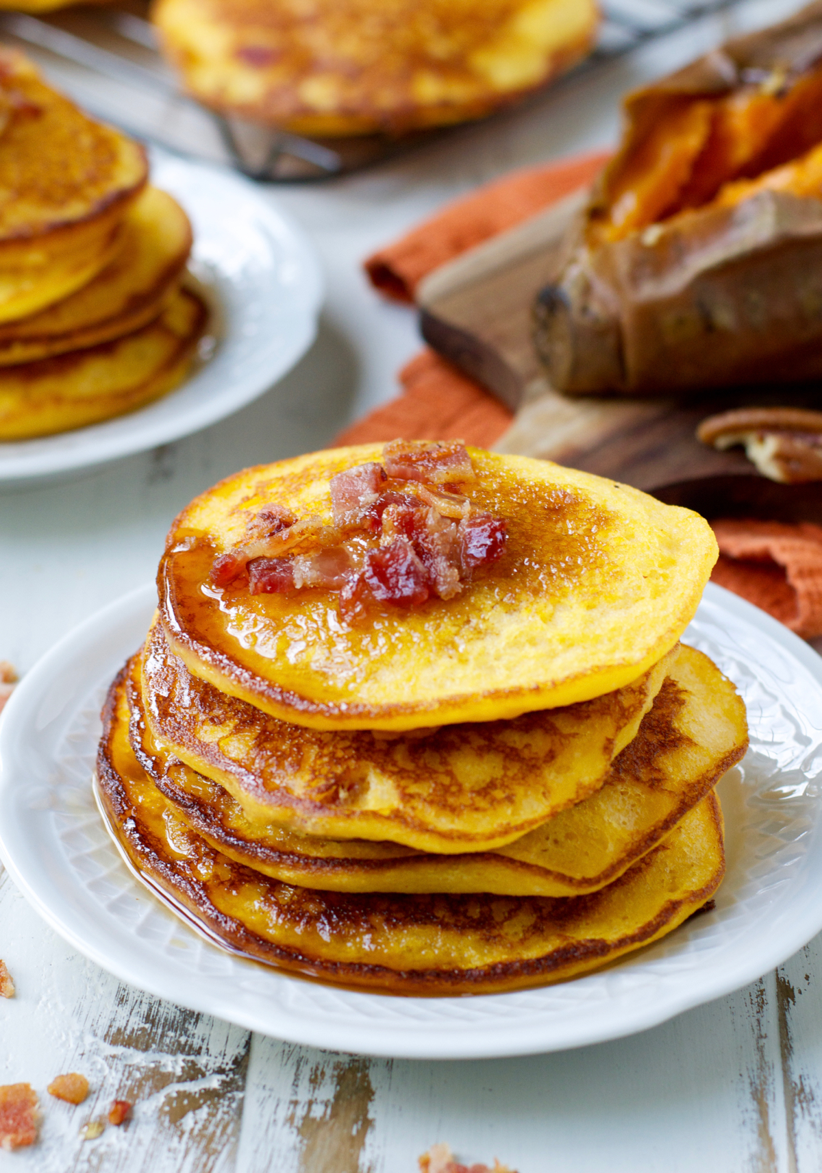 sweet potato and bacon pancakes stacked on a white plate