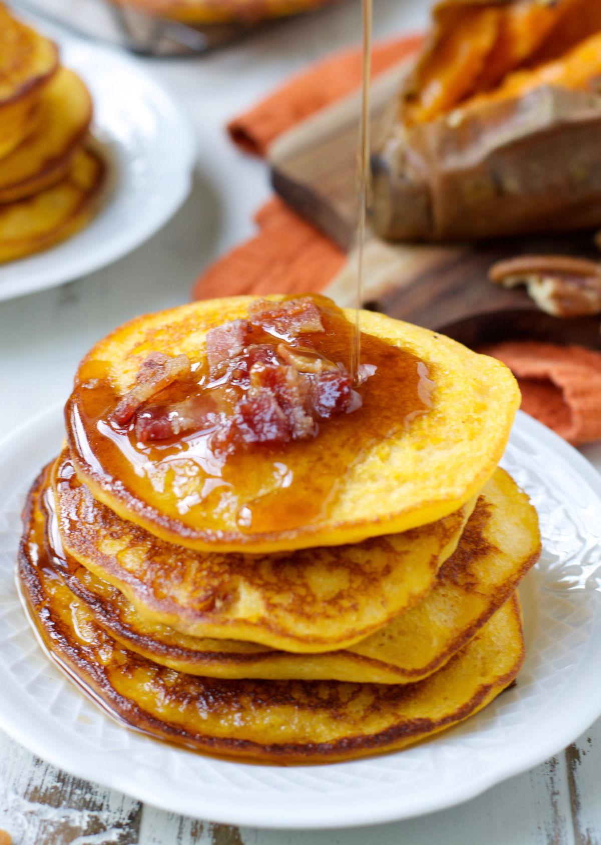 maple syrup being drizzled onto a stack of sweet potato bacon pancakes
