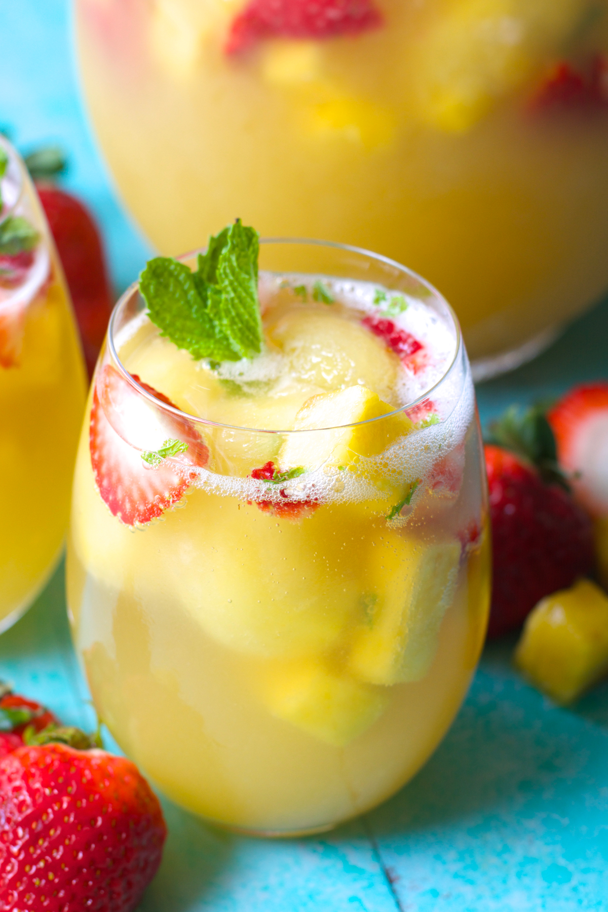 Close up of a glass of strawberry pineapple punch garnished with mint leaves and fresh fruit.