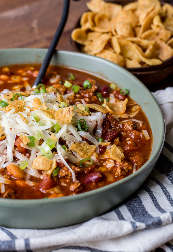 bowl of simple turkey chili topped with Fritos, cheese, and green onions. a bowl of fritos rests in the background