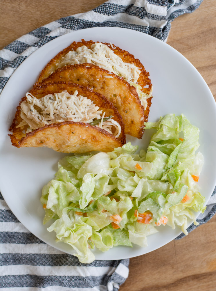 ranch seasoning chicken in two cheese taco shells with a side salad on a white plate.