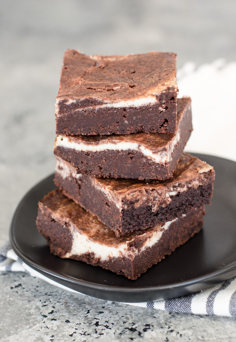 four keto brownies stacked on a gray plate