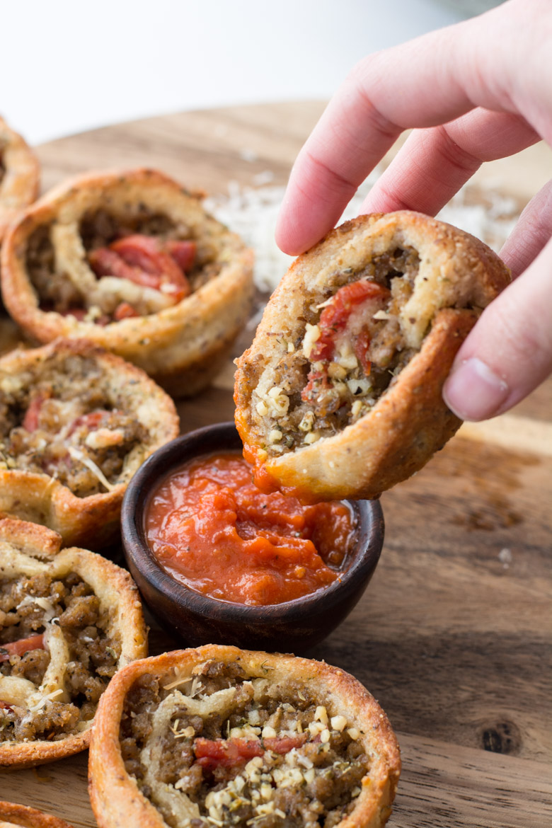 a keto pizza roll up being dunked into marinara sauce