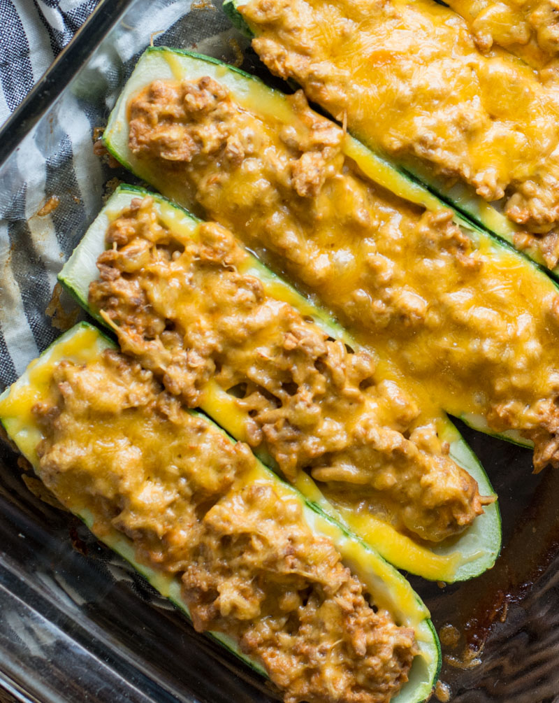 overhead view of three cheeseburger ground beef zucchini boats in a glass baking dish
