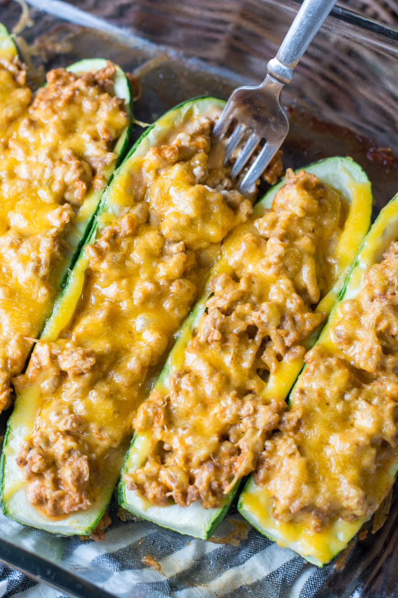 overhead view of keto zucchini boats in a baking dish. a fork is being dug into one.