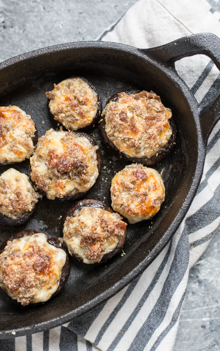 sausage and cream cheese stuffed mushrooms in a cast iron pan