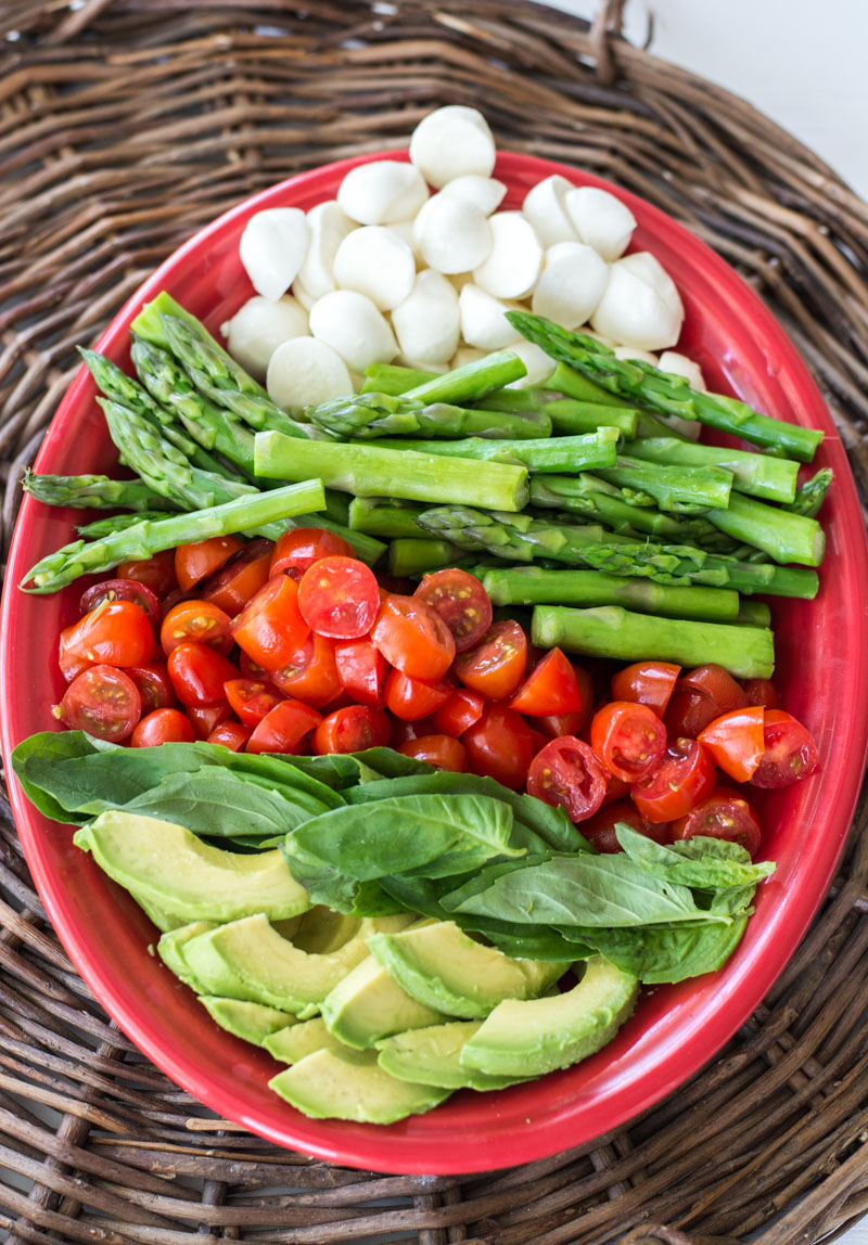 Overhead view of the ingredients for a cold asparagus salad in a red serving dish.